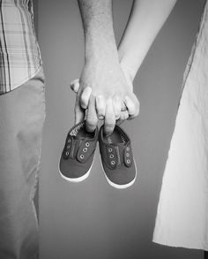 expecting parents holding baby shoes